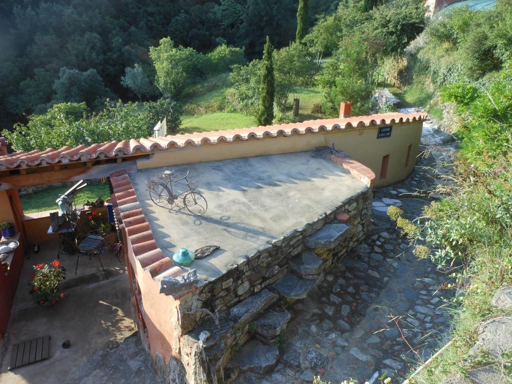 L'arrière-cuisine adossée au préau. Le chemin pavé mène au pont sur la rivière et plus loin à Céret