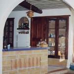 La cuisine vue du séjour. Au sol, carreaux de terre cuite récupérées, briques de terre crue, porte et fenêtres récupérées pour les placards, plafond à la provençale