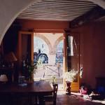 Le séjour depuis la cuisine, au fond la terrasse couverte avec ses arches