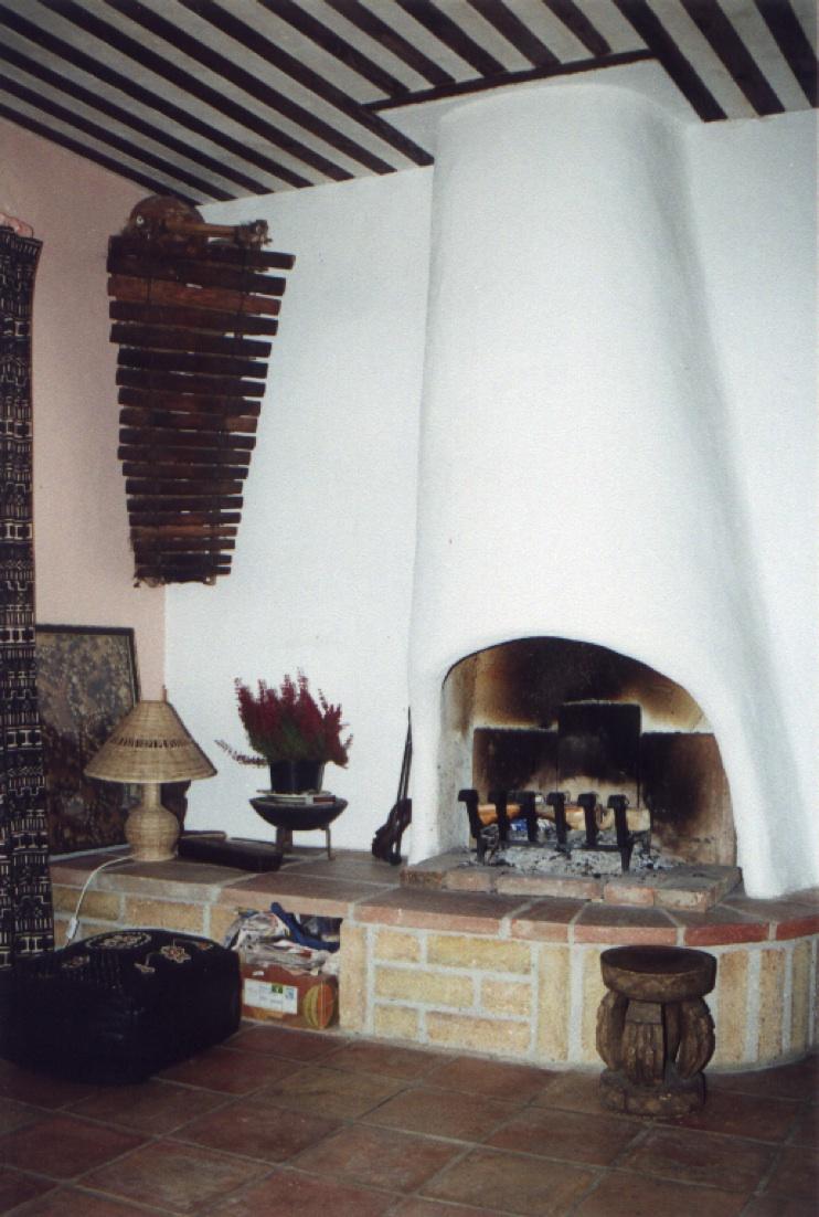 Cheminée en plâtre sur socle en briques de terre crue et foraines